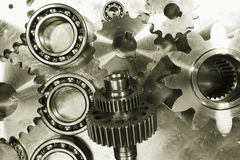 Titanium and steel gears and ball-bearings. Industrial gears and bearings against titanium background, duplex bronze toning concept royalty free stock photos