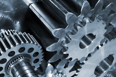 Titanium and steel gears and cogs. Large steel gears set against a brushed titanium background Royalty Free Stock Image