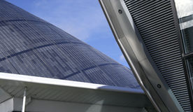 Titanium wedge. The titanium roofs of two modern buildings intersect against a blue sky royalty free stock photography