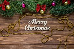 Titel der frohen Weihnachten auf der Mitte des hölzernen Hintergrundes mit Lametta und einem goldenen Chaplet herum Stockfotografie