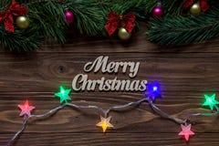 Titel der frohen Weihnachten auf der Mitte des hölzernen Hintergrundes mit Lametta und funkelnden Girlanden Vektor - einfach zu b Lizenzfreies Stockbild