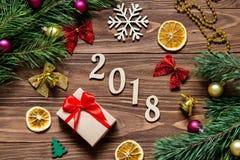 Titel des neuen Jahres 2018 auf dem luxuriösen Holztisch umgeben mit Weihnachtsgeschenk, Scheiben der Zitrone, Glocken und andere Stockfotos