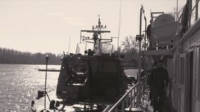Preparing on a warship for action. Titel ; Serbia ; 11/11/2018.Warships of a river fleet anchored in a military base.Contemporary video processed to look like an stock footage
