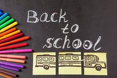 Titel zurück zu der Schule geschrieben durch Kreide und Bild des Schulbusses gezeichnet auf die Blätter Papier auf die Tafel Lizenzfreie Stockfotografie