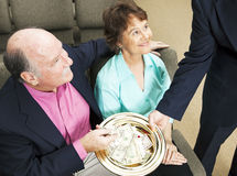 Tithing in Church. Church members placing money in the collection plate Stock Photography
