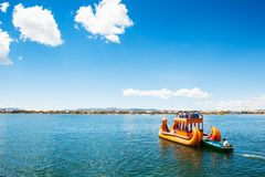 Traditional Totora boat on Titicaca lake in Puno, Peru. Titicaca lake, Puno, Peru - March, 20, 2017. Traditional Totora boat with tourists near Uros floating Stock Images