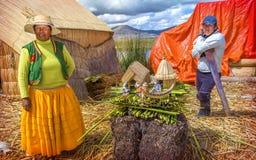 TITICACA, PERÚ - 29 DE DICIEMBRE: Mujer india y hombres que venden puerta a puerta sus mercancías Foto de archivo libre de regalías