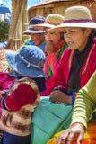 TITICACA, PERU - 29 DE DEZEMBRO: Mulheres indianas que vendem de porta em porta seus mercadorias em um re Fotografia de Stock Royalty Free