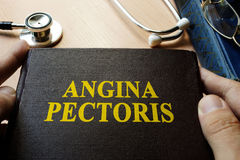 Title Angina pectoris on a book. Title Angina pectoris on a book which holding doctor Stock Photography
