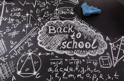 Title Back to school,  formulas written by white chalk on the black school chalkboard and blue rag for erasing Royalty Free Stock Photography