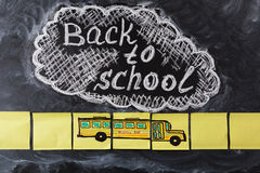 Title Back to school written by chalk on the chalkboard and the school bus drawn on  pieces of paper Royalty Free Stock Images