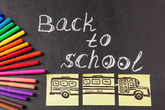 Title Back to school written by chalk and image of the school bus drawn on the pieces of paper on the chalkboard Royalty Free Stock Photography