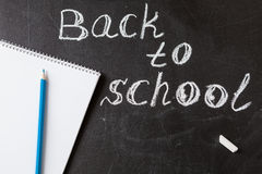 Title Back to school written by white chalk and the the notebook with blue pencil  on the black school chalkboard Stock Photography