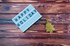 Title Happy Holiday and gold pine tree laying on brown wooden background Royalty Free Stock Image