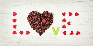 Title LOVE of coffee beans and many little red hearts on the woo Royalty Free Stock Photos