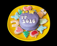 The title PF 2016 written on festive cake with various gingerbre Royalty Free Stock Photos
