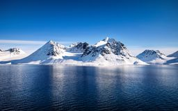 Svalbard mountains and fiords. Blue sky, blue and snowy mountains in the beautiful fjords of Svalbard, a Norwegian archipelago between mainland Norway and the royalty free stock images