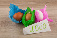Title uovo and chicken eggs in paper laying on wooden table Stock Photo