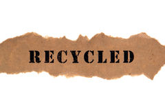 Title Word Recycled on Brown Paper Banner. The environmentally correct title word recycled typed on a piece of eco friendly natural fiber content unbleached Royalty Free Stock Photo