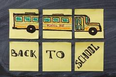 Titres de nouveau à l'école et à l'autobus scolaire écrits sur les morceaux de papier jaunes sur le tableau noir d'école Image libre de droits