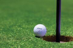 Titrist Golf Ball Near Golf Hole Royalty Free Stock Photos