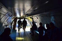 Tittare undersöker den militära inre för hantverket An-26 Arkivfoto