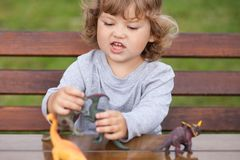 Toddler kid playing with a toy dinosaurs outdoors. Tittle girl having fun playing in dinosaurs fight outdoors Royalty Free Stock Image