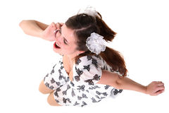 Tittle-tattle. A young girl sits on the floor and talks by a mobile phone Royalty Free Stock Images