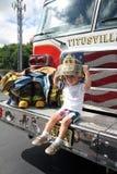 Titusville NJ,美国 07 05 2015年 使用与消防员成套装备和坐在救火车的一个年轻男孩 库存图片