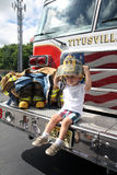Titusville NJ USA 07 05 2015 En ung pojke som spelar med brandmandräkter och sitter i en firetruck Arkivbilder