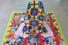 Tivaevae on empty chair Rarotonga Cook Islands. Tivaevae on empty chair.  Tivaevae is a form of artistic quilting traditionally done by Polynesian women Stock Image