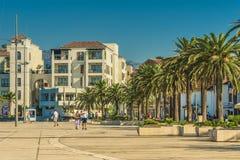 TIVAT, MONTENEGRO - 24. August 2017: Auf dem Kai von Tivat, Montenegro, mit schönen Palmen, promenieren Seeschiffe gegen t Lizenzfreie Stockbilder