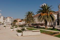 TIVAT, MONTENEGRO - 9 DE NOVEMBRO DE 2018: Turistas que andam na frente mar?tima ensolarada da cidade de Tivat imagens de stock royalty free