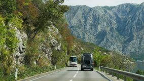 Passenger bus traveling on a mountain road in Montenegro. Tivat, Montenegro - September 26: a passenger bus traveling on a mountain road in the European day of stock video