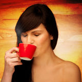 Tive young woman with black hair holding red cup of coffee in he Royalty Free Stock Photography
