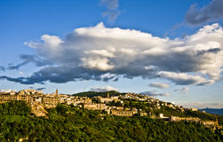 Tivoli town on hillside. Scenic view of Tivoli town on forested hillside under dramatic cloudscape, Italy Royalty Free Stock Image