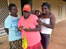 Tiwi kvinnor och behandla som ett barn kontrollera telefonen Arkivbilder