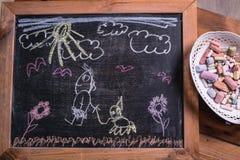 Tiza de dibujo del ` s de los niños en una pizarra imágenes de archivo libres de regalías