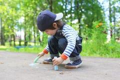 Tiza de dibujo linda del niño pequeño en la tierra Fotos de archivo libres de regalías