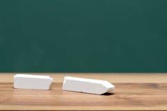 Tiza quebrada en el escritorio del profesor delante del tablero Fotos de archivo