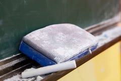 Tiza y cepillo que se reclinan sobre tarjeta negra Imagenes de archivo