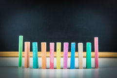 Tizas y pizarra coloridas Imagenes de archivo
