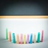 Tizas y pizarra coloridas Imagen de archivo