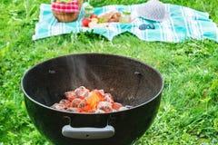 Tizzoni quasi pronti da cucinare in una griglia rotonda ad un picnic su un patio all'aperto immagine stock