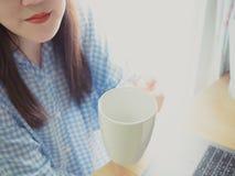 Tjäna som den vita koppen kaffe för drink i morgontid i hand av b royaltyfri foto