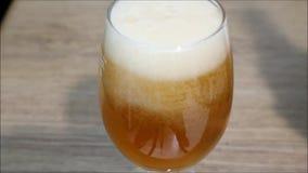Tjäna som ett exponeringsglas av blont öl med mossa lager videofilmer