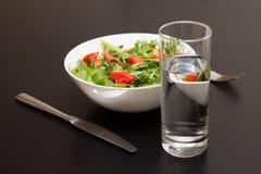 Tjäna som med ljus sallad med tomater och ett exponeringsglas av vatten Arkivfoto