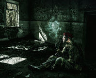 Tjäna som soldat den bärande militära likformign i den förstörda byggnaden Arkivbild