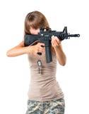 Tjäna som soldat den unga härliga flickan med ett vapen i hans hand på vit arkivbilder