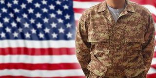 Tjäna som soldat i en amerikansk militär digital modelllikformig som står på en USA flaggabakgrund royaltyfri bild